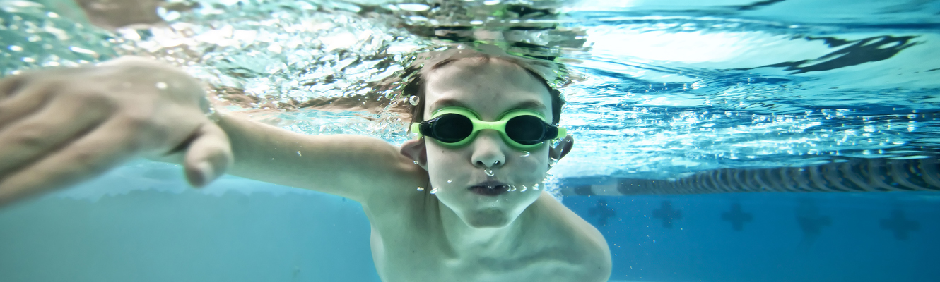 Young boy swimming underwater with goggles