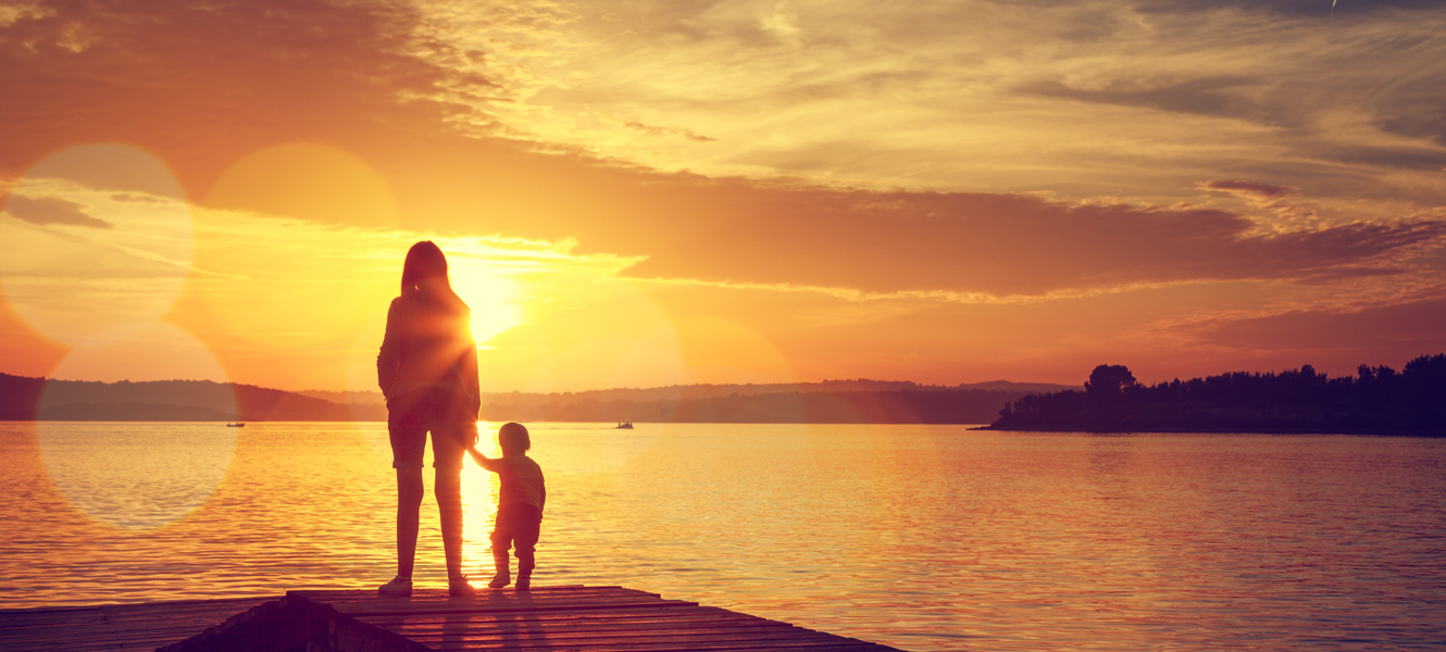 Photo of Mom and Child on river dock watching a beautiful sunset