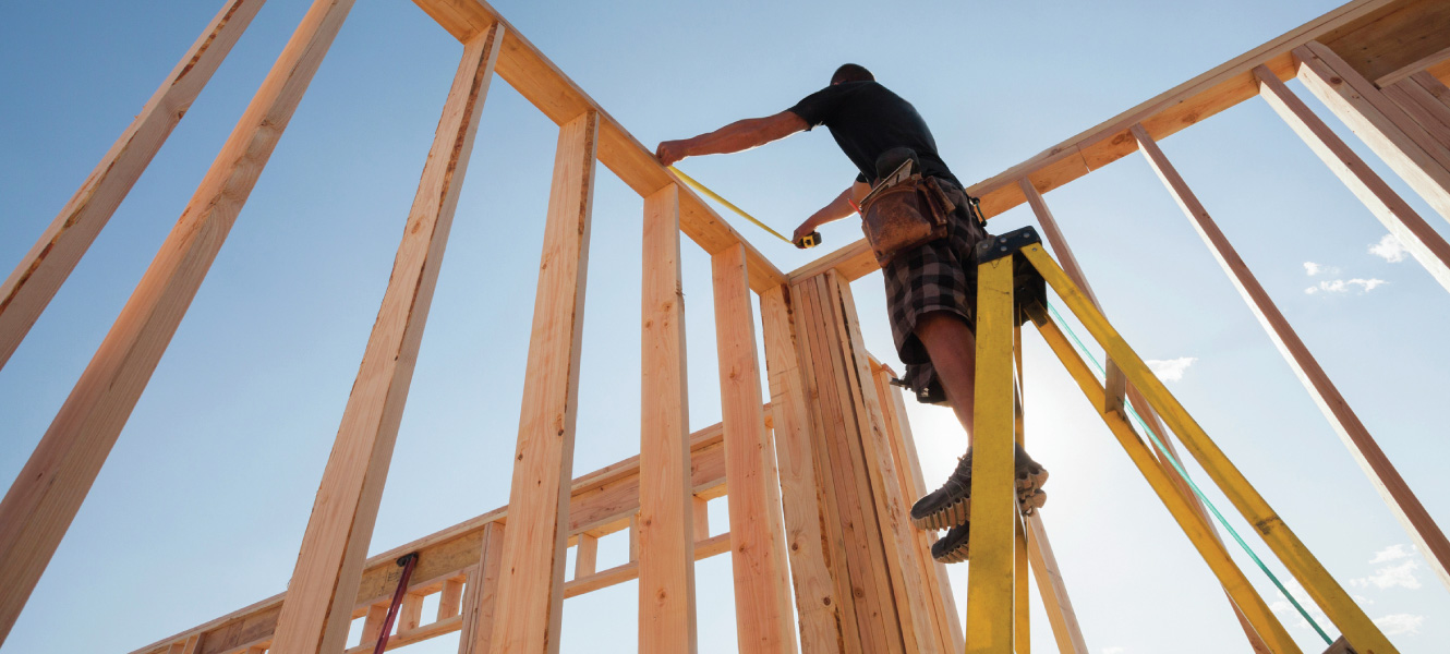 A carpenter framing a house.